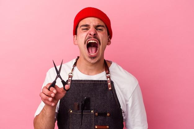 Młody fryzjer kaukaski mężczyzna trzyma nożyczki na białym tle na różowym tle krzycząc bardzo zły i agresywny.