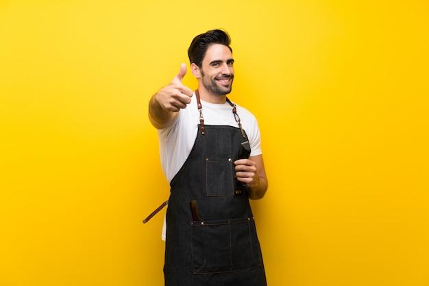Młody fryzjer mężczyzna na pojedyncze żółte ściany z kciuki do góry, ponieważ stało się coś dobrego