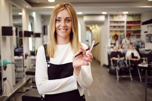 Młody fryzjer w swoim własnym salonie piękności, gdzie ludzie są uczęszczani z tyłu