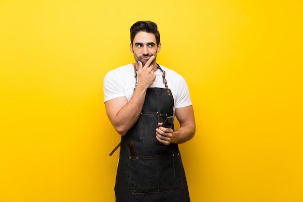 Młody fryzjera mężczyzna nad odosobnioną kolor żółty ścianą myśleć pomysł