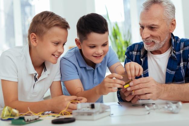 Młody geniusz. mili, pozytywni chłopcy budujący robota i jednocześnie cieszący się inżynierią