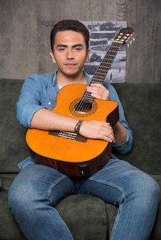 Młody gitarzysta trzymając piękną gitarę i siedząc na kanapie. wysokiej jakości zdjęcie