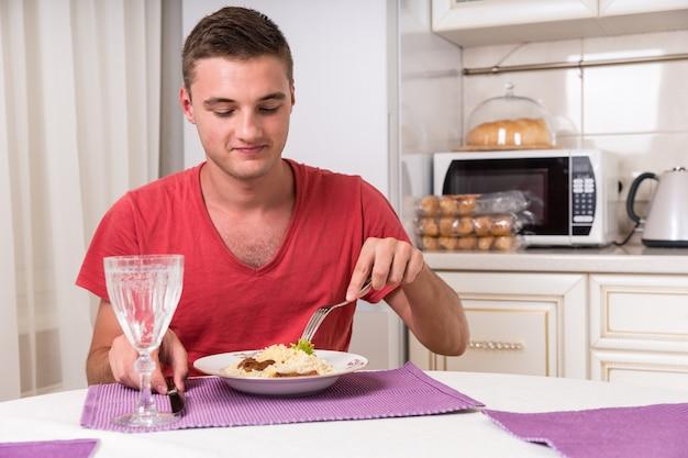 Młody głodny mężczyzna wbijający się w talerz makaronu siedząc przy stole w uroczej kuchni podczas kolacji
