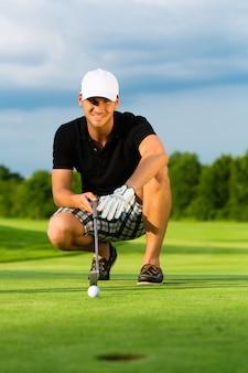 Młody golfista na polu golfowym