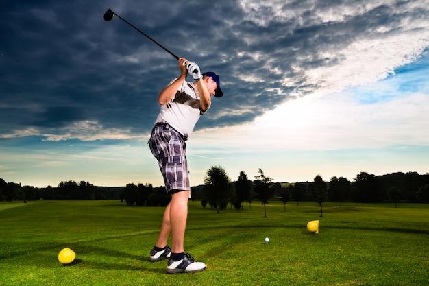 Młody golfowy gracz na polu robi golfowej huśtawce