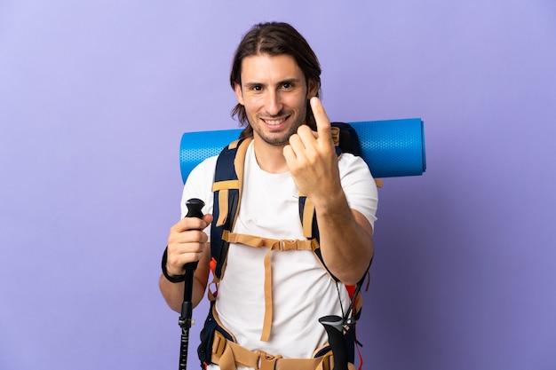 Młody góral człowiek z dużym plecakiem na odizolowanej ścianie robi nadchodzący gest
