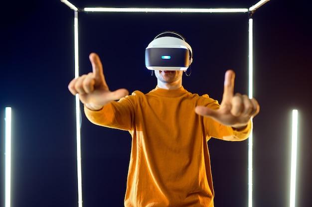 Młody gracz gra za pomocą zestawu słuchawkowego do rzeczywistości wirtualnej i gamepada w świecącej kostce, widok z przodu