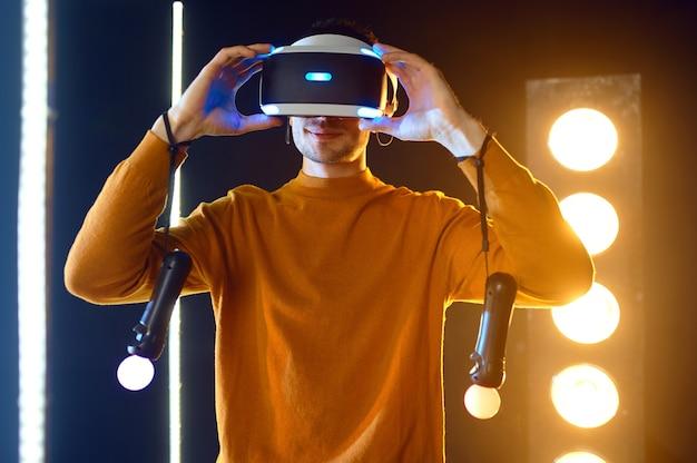 Młody gracz gra za pomocą zestawu słuchawkowego rzeczywistości wirtualnej i gamepada w świecącej kostce