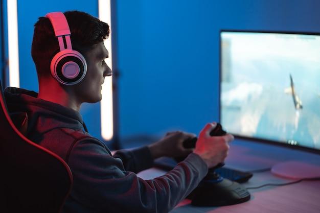 Młody gracz grający w gry wideo online na swoim komputerze osobistym