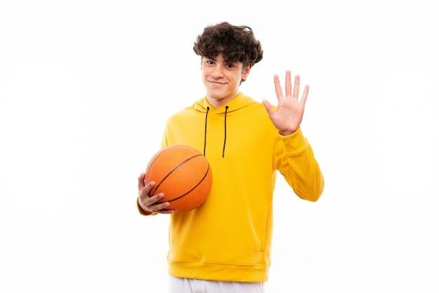 Młody gracz koszykówki mężczyzna nad odosobnioną biel ścianą salutuje z ręką z szczęśliwym wyrażeniem