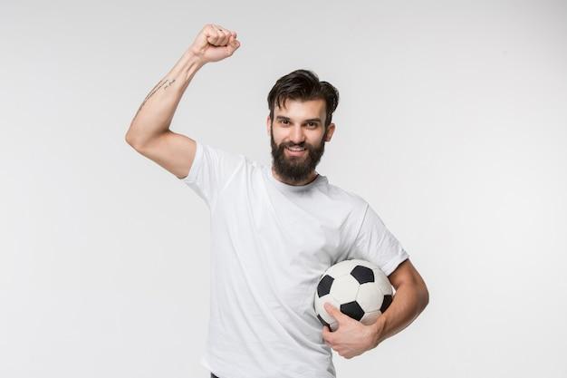 Młody gracz piłki nożnej z piłką przed biel ścianą
