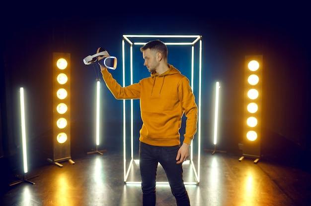 Młody gracz pozuje z zestawem słuchawkowym do rzeczywistości wirtualnej i gamepadem w świecącej kostce, widok z przodu