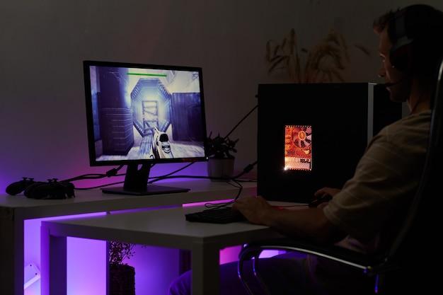 Młody gracz w słuchawkach siedzi przy stole przed monitorem komputera i grając w gry komputerowe