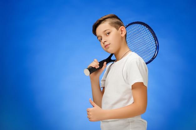 Młody gracz w tenisa na błękit ścianie
