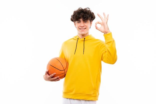 Młody gracza koszykówki mężczyzna nad odosobnioną biel ścianą pokazuje ok znaka z palcami