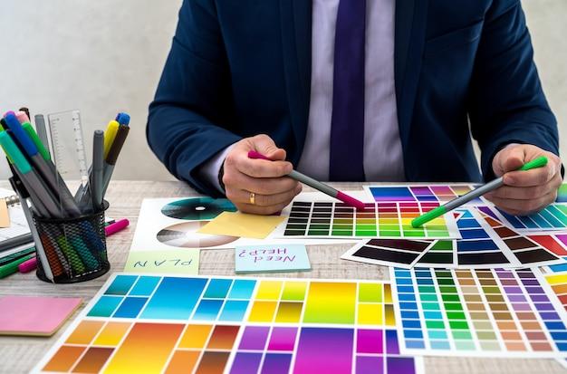Młody grafik lub projektant wnętrz w garniturze wybiera kolor z próbki lub przewodnika po palecie katalogowej w miejscu pracy. grafik z próbkami palety kolorów farb przy stole, z bliska