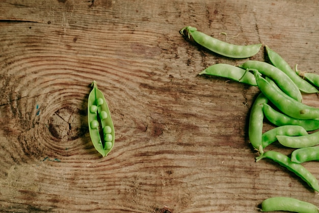 Młody groszek na drewnianym tle. widok z góry. zdrowa przekąska. jedzenie wegańskie. groszek otwarty