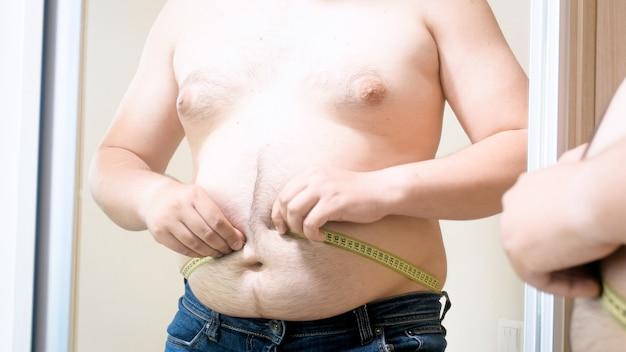 Młody grubas z dużym brzuchem walczy o zmierzenie jego rozmiaru. pojęcie męskiej nadwagi, odchudzania i diety.