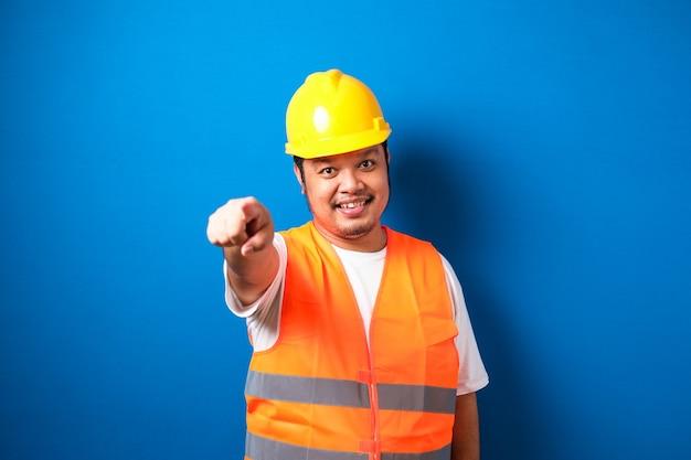 Młody gruby azjatycki pracownik budowlany mężczyzna nosi hełm ochronny wskazujący palcem