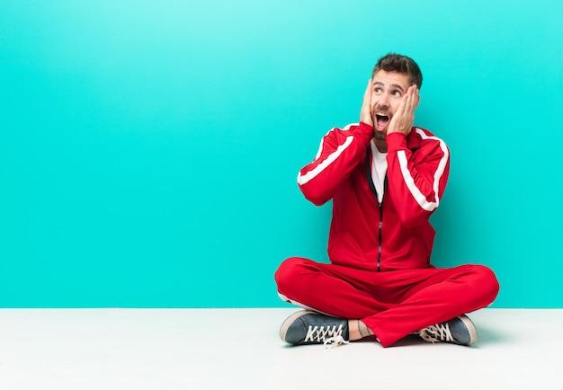 Młody handosme człowiek czuje się szczęśliwy, podekscytowany i zaskoczony, patrząc z boku obiema rękami na twarzy na tle płaskiego koloru ściany