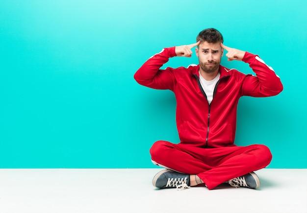 Młody handosme człowiek o poważnym i skoncentrowanym wyglądzie, burzy mózgów i myślenia o trudnym problemie z płaską ścianą koloru