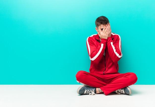 Młody handosme czuje się przestraszony lub zawstydzony, zerkając lub szpiegując oczy na wpół pokryte rękami o płaskiej ścianie