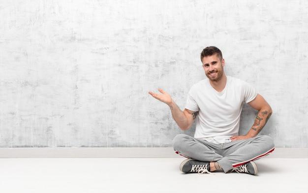 Młody handosme mężczyzna ono uśmiecha się, czuje się ufny, pomyślny i szczęśliwy, pokazuje pojęcie lub pomysł na kopii przestrzeni na stronie przeciw płaskiej kolor ścianie