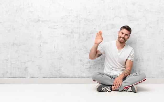 Młody handosme mężczyzna uśmiecha się radośnie i wesoło, macha ręką, wita i wita lub żegna się z płaską ścianą koloru