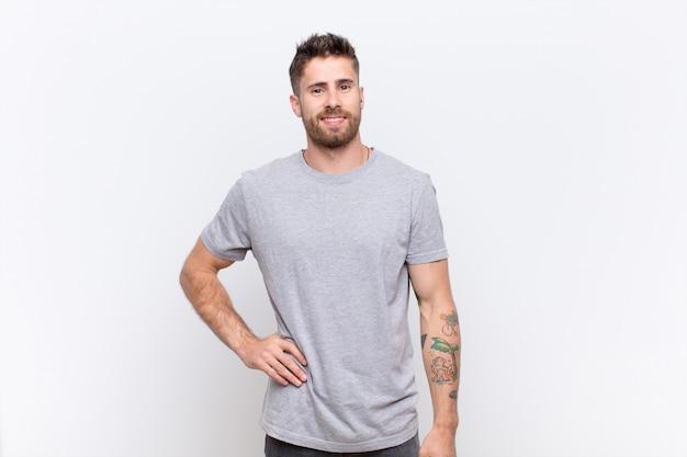 Młody handosme mężczyzna uśmiecha się radośnie z ręką na biodrze i pewny siebie, pozytywny, dumny i przyjazny stosunek do koloru ściany