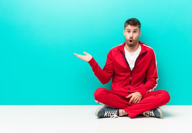 Młody handosme mężczyzna wyglądający na zaskoczonego i zszokowanego, z opuszczoną szczęką trzymającą obiekt otwartą dłonią na boku o płaskiej ścianie