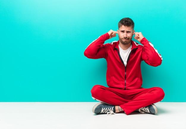 Młody handosme mężczyzna wyglądający na zły, zestresowany i zirytowany, obejmujący uszy ogłuszającym hałasem, dźwiękiem lub głośną muzyką na tle płaskiej ściany