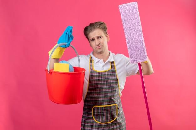 Młody hansdome człowiek ubrany w fartuch i gumowe rękawiczki, trzymając wiadro z narzędziami do czyszczenia i mopem