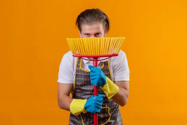 Młody hansdome mężczyzna ubrany w fartuch i rękawice gumowe trzymając mopa, chowając się za nim