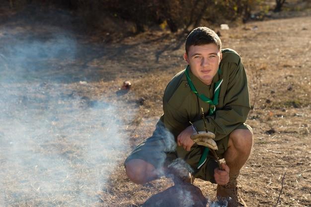 Młody harcerz w mundurze co ogień na kempingu, patrząc w kamerę.