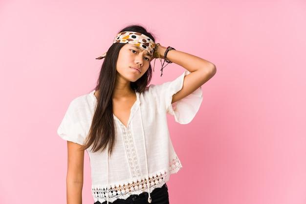 Młody hipis chiński na białym tle dotykając tyłu głowy, myśląc i dokonując wyboru.