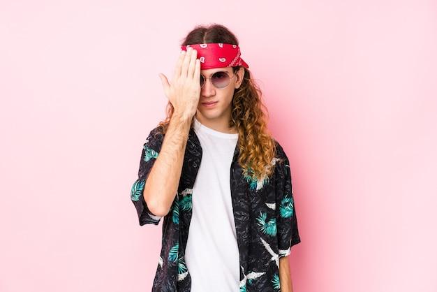 Młody hipis kaukaski mężczyzna na białym tle zabawy obejmujące pół twarzy dłonią.