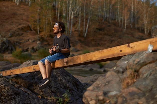 Młody hipis w dżinsowych szortach iz szalikiem na głowie siedzi na moście w pobliżu skał i ...