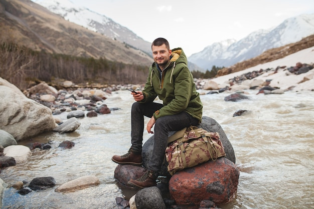 Młody hipster człowiek za pomocą smartfona, dzika przyroda, ferie zimowe, turystyka