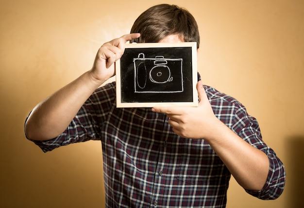 Młody hipster mężczyzna fotografujący za pomocą aparatu namalowanego na tablicy