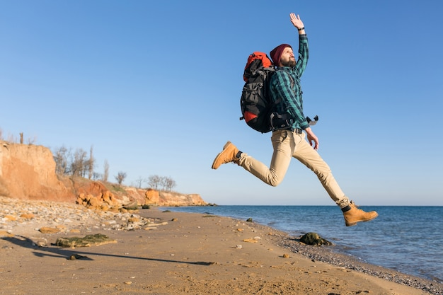 Młody hipster mężczyzna podróżujący z plecakiem na jesiennym wybrzeżu morza w ciepłej kurtce i kapeluszu