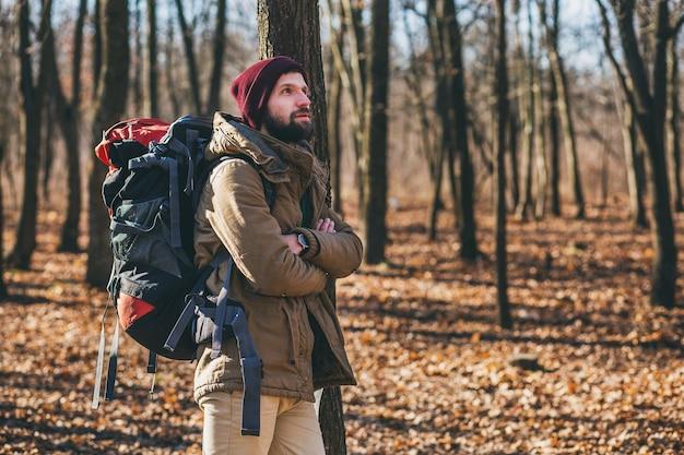 Młody hipster mężczyzna podróżujący z plecakiem w jesiennym lesie, ubrany w ciepłą kurtkę i kapelusz