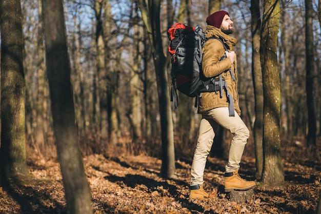 Młody hipster mężczyzna podróżujący z plecakiem w lesie jesienią na sobie ciepłą kurtkę i kapelusz, aktywny turysta, odkrywanie przyrody w zimnych porach roku