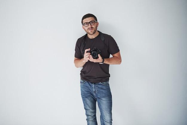 Młody hipster mężczyzna w okularach trzyma lustrzankę cyfrową w rękach stojących na białej ścianie