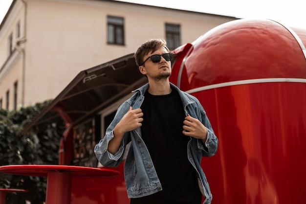 Młody hipster miejski zdejmuje modną kurtkę dżinsową. model atrakcyjny facet w okulary pozuje na tle czerwonej furgonetki z jedzeniem w mieście w słoneczny wiosenny dzień. modna odzież męska.