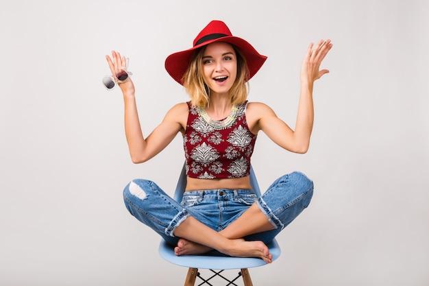 Młody hipster piękna kobieta siedzi na krześle na białym tle