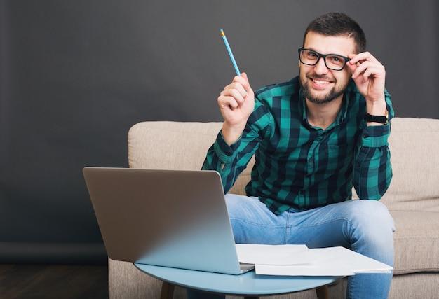 Młody hipster przystojny brodaty mężczyzna siedzi na kanapie w domu