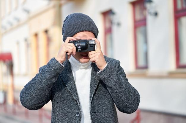 Młody hipster stylowy modny mężczyzna ubrany w szary płaszcz, biały sweter i szary kapelusz z aparatem