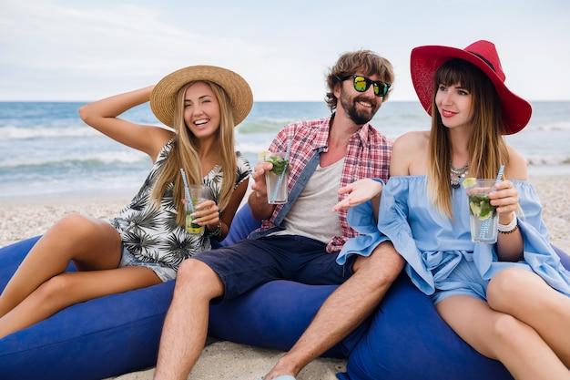 Młody hipster towarzystwo przyjaciół na wakacjach w kawiarni na plaży, pijąc koktajl mojito
