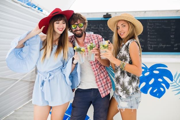 Młody hipster towarzystwo przyjaciół na wakacjach w letniej kawiarni, picie koktajli mojito, szczęśliwy pozytywny styl, uśmiechnięty szczęśliwy, dwie kobiety i mężczyzna bawią się razem, rozmawiają, flirt, romans, trzy