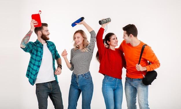 Młody hipster towarzystwo przyjaciół, wspólna zabawa, uśmiechanie się, słuchanie muzyki na głośnikach bezprzewodowych